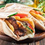 Gyros souvlaki wrapped in a pita bread on cutting board. Greek dish